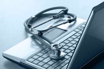 Stethoscope resting on a computer keyboard