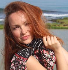 Pretty redhead woman near the beach