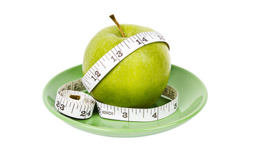 Dieting concept Green apple with measuring tape on green plate