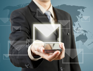 Businessman holding mobile phone and mail
