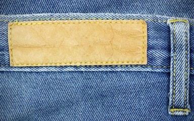 Blank leather jeans label sewed on a blue jeans, used as backgro