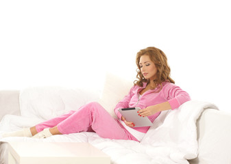 A young woman with a pad relaxing in pink sporty clothes