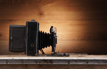 A beautiful old photo camera on a vintage background