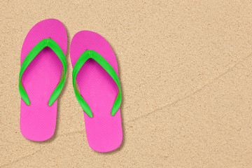 pink and green flip flops on the beach with space