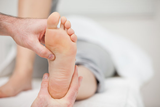 Doctor holding the foot of a woman