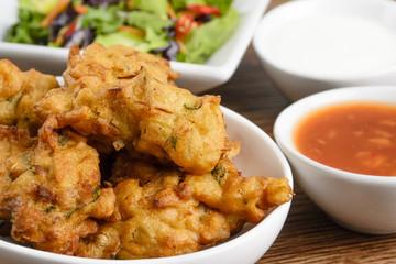 Vegetable Pakora or Bhaji with salad, chili sauce & raita.