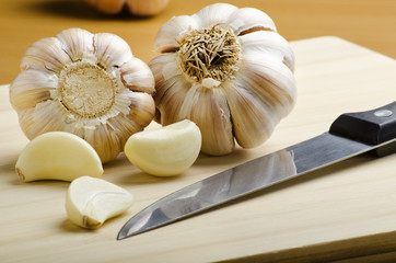 garlics and fruit knife on cutting board