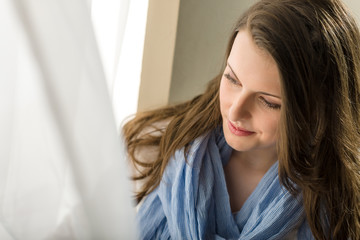 Brunette young woman looking down window