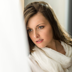 Thoughtful brunette woman looking out of window