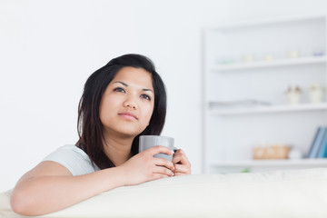 Woman holding a mug as she rests one arm on a sofa