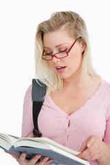 Serious woman wearing glasses while reading a book