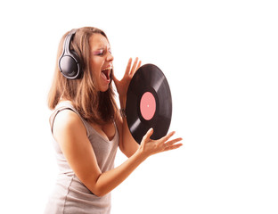 A girl in ear-phones with vinyl is singing - side view