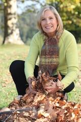 Woman gathering fallen leaves with rake