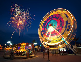 Poster Attraction parc Amusement park at night - ferris wheel in motion and firework