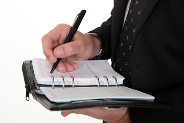 businessman noting down appointment on agenda