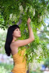 Girl near blossom acacia tree