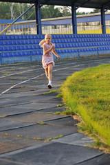 Девочка бегает на стадионе