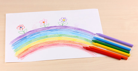 Children's drawing of rainbow and pencils on wooden background