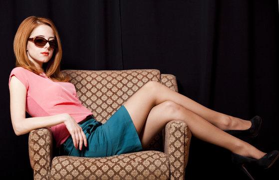 Redhead girl in armchair. 70s
