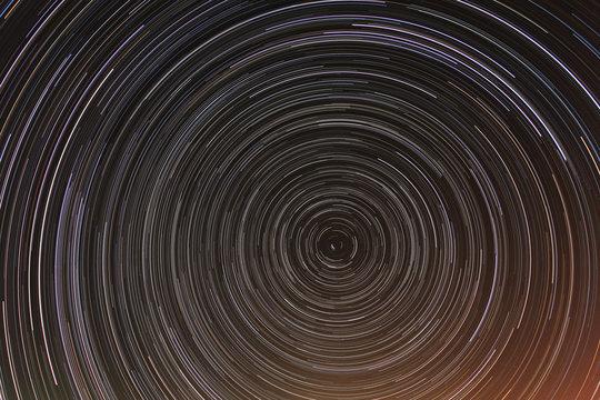 Cumulative time lapse of star trails in night sky.