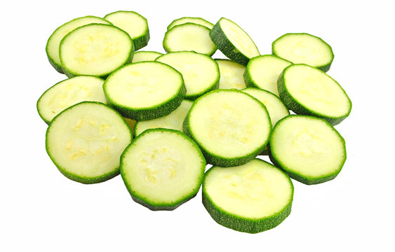slices of zucchini piled on white background