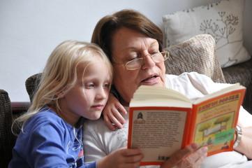 Großmutter ließt Enkeltocher etwas aus einem Buch vor