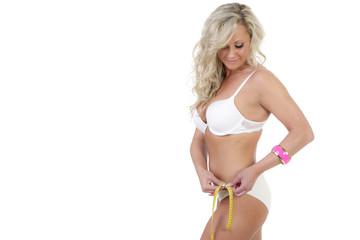Hübsche blonde Frau kontrolliert mit Maßband Umfang vom Taille