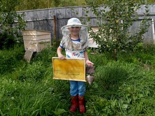 Юный пчеловод с рамкой и дымарём