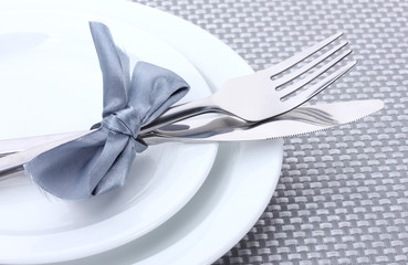 White empty plates with fork and knife tied with a ribbon