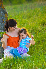 mother, daughter, woman and child sitting in grass near a tree a