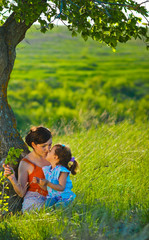 mother, daughter, woman and child sitting in the green grass nea