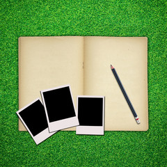 Pencil and photo frame with old book on green grass background