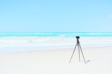 Digital Camera and tripod on white beach for landscape photograp