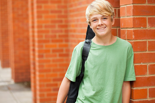 happy male teen musician carrying his guitar