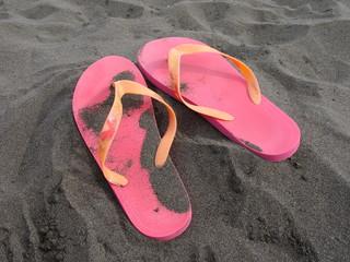 Sandalen im schwarzen Sand