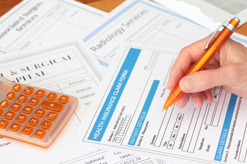 Hand completing a health insurance claim with invoices
