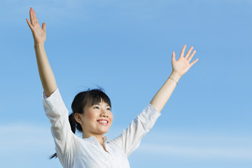 Happy Asian woman with arms raised upwards