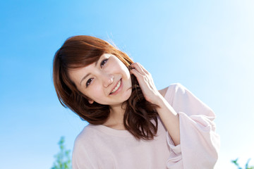 Beautiful young woman outdoors over blue sky. Portrait of asian