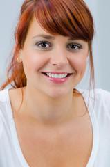portrait einer lächelnden rothaarigen jungen frau