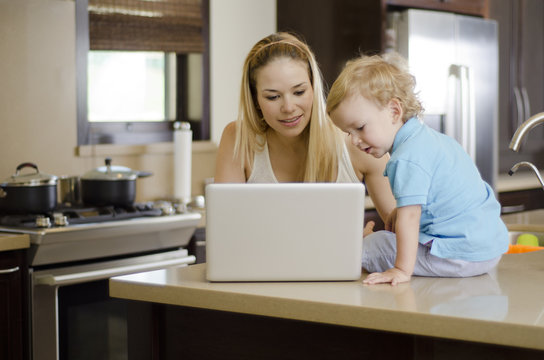 Mom showing something to her son on a computer