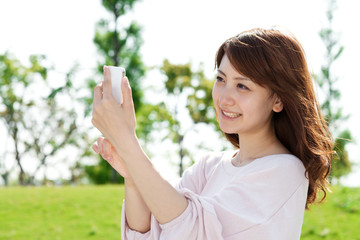Beautiful young woman using a moblie phone in a park