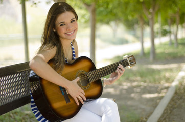 Cute girl playing the guitar on a park bench