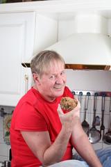 Mann isst ein Laib Brot in einer Küche
