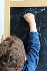 enfant dessinant sur un tableau