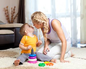 loving mother kissing her child boy together indoor
