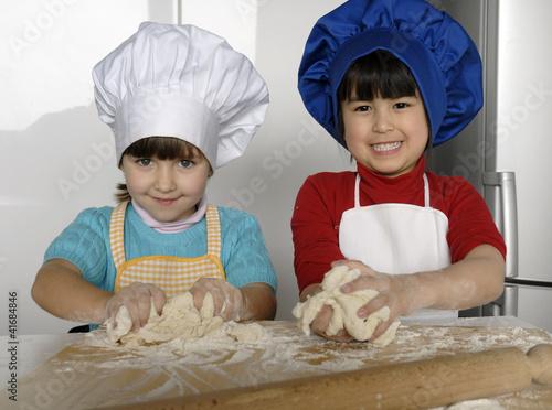 Dos ni as cocinando masa y pizza en una cocina fotos de - Nina cocinando ...
