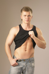 Young man pointing at his abs isolated on grey background