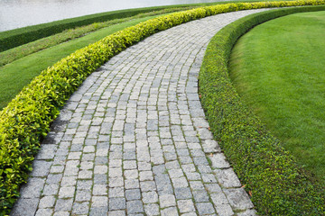 The Stone block walk path in the park with green grass backgroun