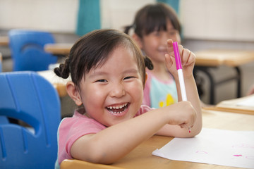 happy little girls drawing picture in the classroom