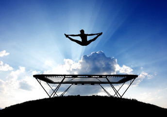 Wall Mural - silhouette of female gymnast on trampoline in front of clouds